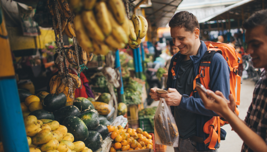 Traveler buying food at market with healthy gut