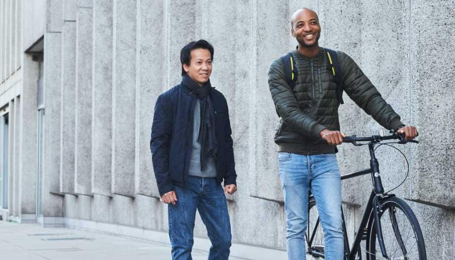 Hombres caminando por la ciudad con bicicleta hablando de economía sanitaria y probióticos