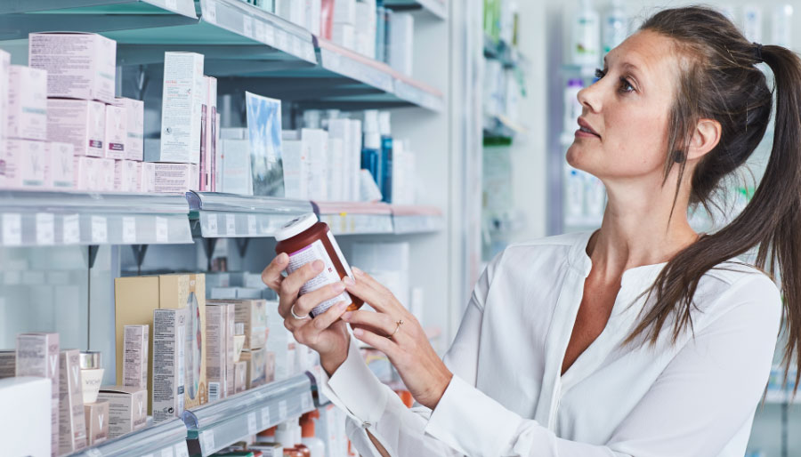 Woman choosing between probiotics products