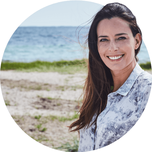 Woman smiling and standing on a beach