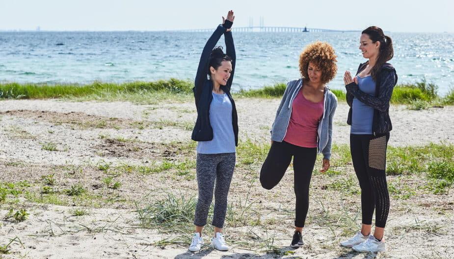 Three women exercising on a beach